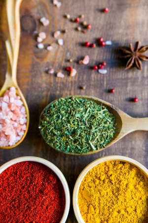 Close up wooden bowls and spoon filled with paprika, rosemary, pink salt and turmeric Stock Photo