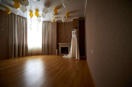 Interior of empty room with baloons and beautiful wedding dress on hanger