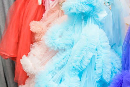 Colorful dresses hang on rack close up