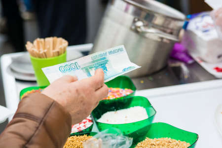 Hand holds bank note for dessert