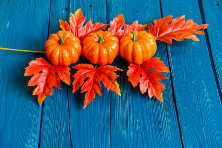 Three plastic pumpkins and red leaves fall concept