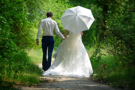 Bride and groom walk in park back view Stock Photo