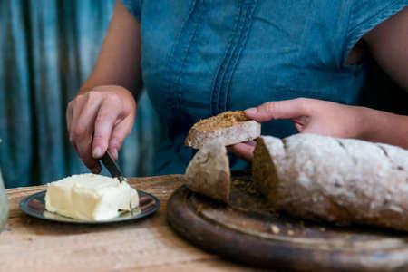 Woman puts butter on rye bread breakfast concept