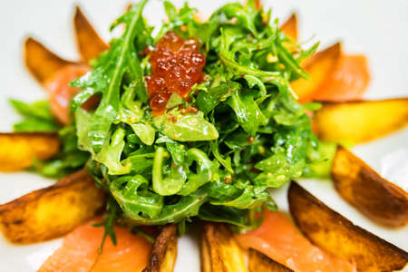 Salad with potato wedges and red caviar