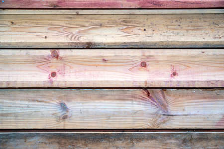 Texture of pinkish wooden planks with some spaces between them