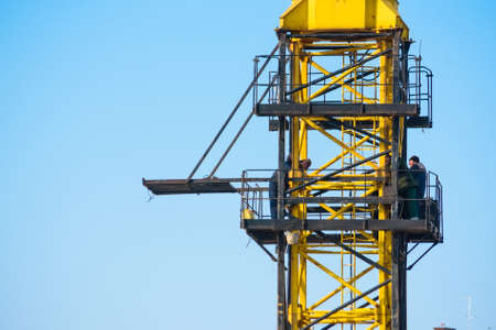 Builders work on yellow crane at construction site