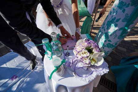 Groom and bride register marriage outdoors closeup