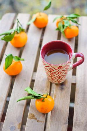 Close up tea mug with vitamin drink and tangerines
