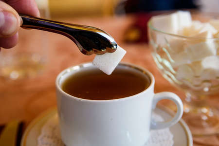 Adding lump of sugar with tweezers to tea in cup