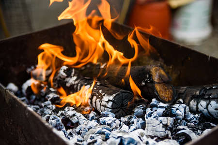 Burning logs in brazier at daylight Stock Photo