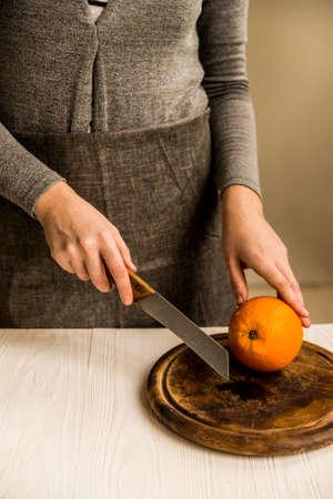 Woman cuts orange on board close