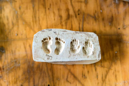 Clay imprints of feet and hands Stock Photo