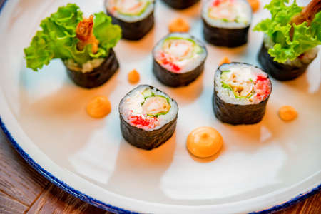 Fresh sushi rolls served on plate in restaurant