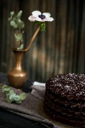 Dark vintage stillife with chocolate cake and vase 写真素材