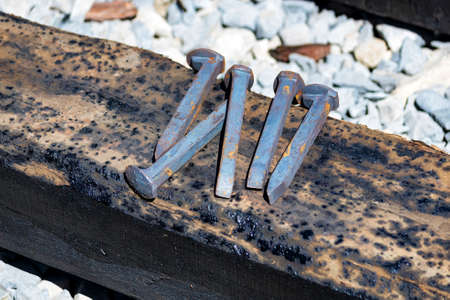 Close up of railroad spikes on wooden sleeper