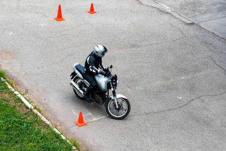 Man is practicing driving a motorcycle in a driving school 免版税图像