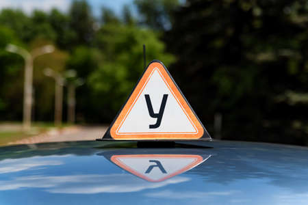 Russian driving school car sign on top of car