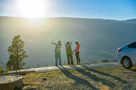 Back view family of tourists enjoy view in mountains