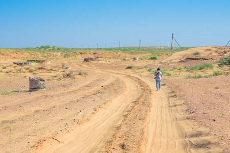 Back view hiker photographer walks on road in semi-desert