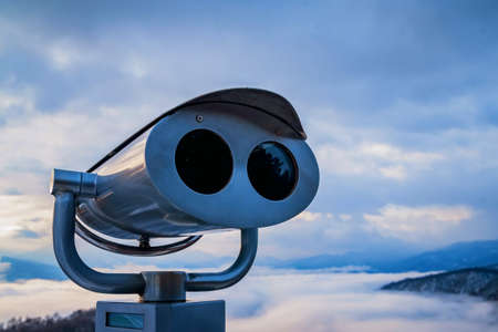 Coin-operated binoculars or tower viewre in beautiful winter mountains