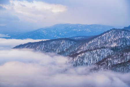 Beautiful distant winter mountains and skyscape with mist