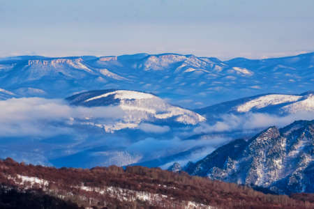 Beautiful distant winter mountains landscape with mist