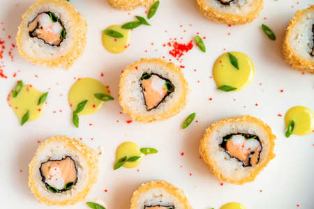 Sushi rolls scattered on white background close up