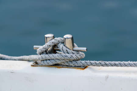 Close up of boat rope tied to nautical cleat hitch on boat