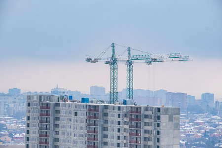 Construction of the new building. Two cranes in winter 写真素材