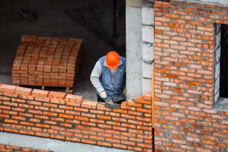 View of mason laying bricks at construction site