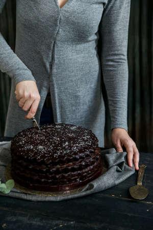 Woman cuts chocolate cake close. Dark tones