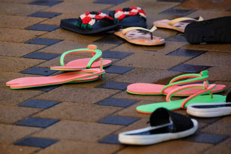 Several pairs of flip-flops next to open pool in winter Stock fotó