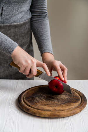 Woman cuts red apple on board close Stock fotó