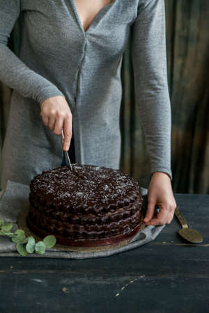Woman cuts chocolate cake close. Dark tones