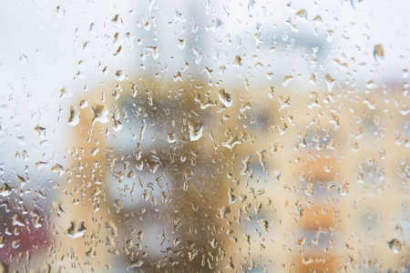 Rain drops on window glass surface with modern appartment building in background
