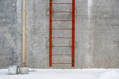 View of red metal ladder outside of a concrete building Stockfoto - 123095702