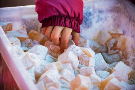 Close up a kids hand grabbing oriental sweets or Turkish delight lokum with powdered sugar Stock fotó