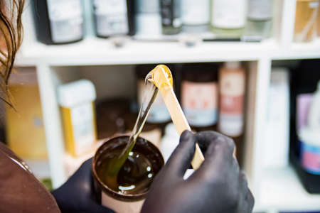 Beauticians hand with glove holding a roll on liposoluble wax cartridges from honey on waxing wooden spatula