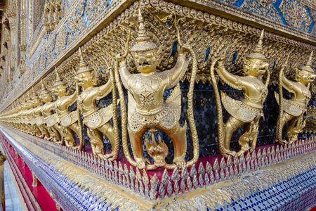 seized: STATUE OF GARUDAS SEIZED NAGA DECORATED ON THE TEMPLE WALL OF THE EMERALD BUDDHA,          GRAND PALACE,               BANGKOK,THAILAND Stock Photo