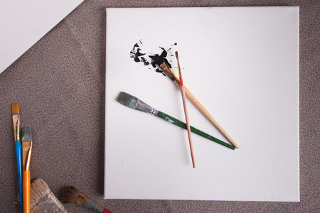 Workspace for an artist paint brushes and white canvas Stock Photo