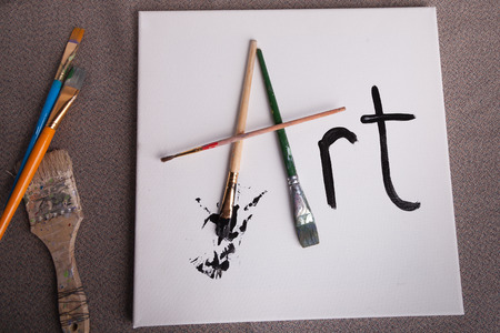 Artist work station with white canvas and art written in paint brushes and black paint Stok Fotoğraf