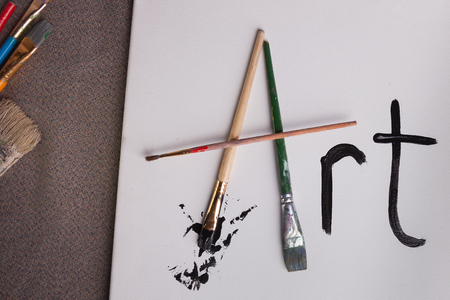 Art written with paint brushes and black paint splatter
