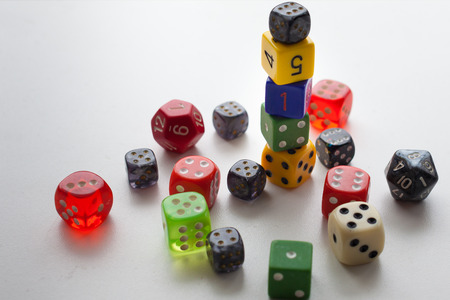 Close up gaming dice stacked and randomly placed on solid background Stock Photo