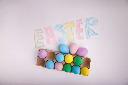 Easter written in chalk with pastel colored Easter eggs in egg carton 写真素材