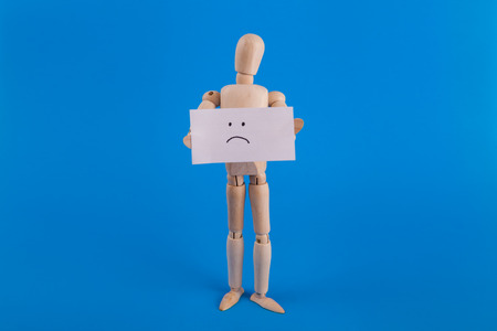 sad face sign held by emotionless wooden jointed doll Stock Photo