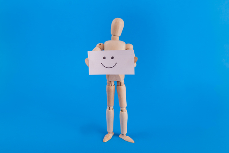 smiley face sign held by wooden jointed doll on solid blue background Banque d'images - 104275564