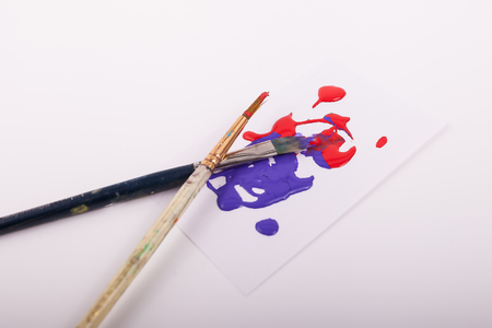 Two paint brushes on white canvas red and purple paint splatters