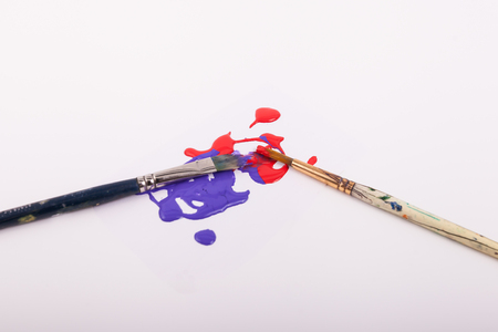 Close up of paint brushes red and purple paint splatters