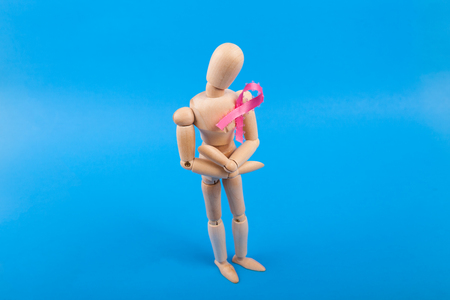Jointed wooden doll with breast cancer awareness ribbon