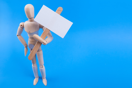 blank protester picket sign held by a wooden jointed manikin on a solid blue background Stock Photo